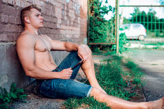 A modern male bodybuilder in shorts is sitting on street with a tablet and headphones, listening to music enjoys outdoor Stock Photos