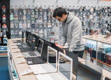 Modern male customer choosing laptop in the computer store. Smart modern male customer choosing laptop in the computer store. difficult decision stock image