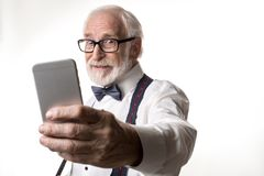 Modern male pensioner taking photo on smartphone. Waist up portrait of joyful elderly man making selfie, looking amused. Focus on face and phone. on background stock image