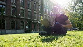 Modern male student or freelancer working on a laptop, sitting in a park on green lawn in campus stock video