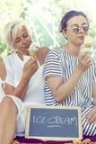 Modern mamma och barndotter som äter glass Fotografering för Bildbyråer