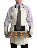 Modern Man. Image of a man against a white background, wearing a kitchen apron and oven mitts over business attire. He is holding a cookie sheet full of freshly stock photos