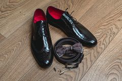 Brown bow tie lies on a belt, leather shoes. Grooms wedding morning. Modern man accessories. Brown bow tie lies on a belt, cufflinks, leather shoes on a wooden Stock Photography