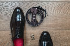 Brown bow tie lies on a belt, leather shoes. Grooms wedding morning. Modern man accessories. Brown bow tie lies on a belt, cufflinks, leather shoes on a wooden Royalty Free Stock Image