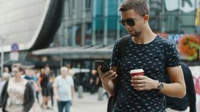 Modern man with a cup of coffee use mobile phone on crowded city street stock footage