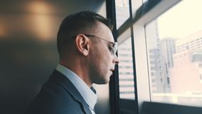 Modern man descending by elevator with transparent walls. Business man in lift stock video footage