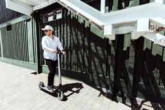 Modern man dressed white shirt and black pants standing at the street with electric scooter stock photos