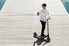 Modern man dressed white shirt and black pants using his phone while standing at a wooden pier with electric scooter stock photography