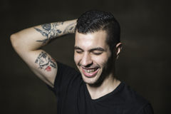 Modern man för ung 20-tal som poserar på den smutsiga väggen Arkivbilder