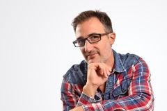 Modern man interesting with hand on chin looking straight ahead. Portrait for concept of visual correction with glasses. Horizontal composition royalty free stock photography