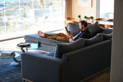 Modern man lazing on the couch of a luxurious apartment Stock Photography