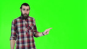 Modern man with a pigtail pointing. Modern bearded man with a pigtail pointing with both hands towards blank copy space on a bright green background, upper body stock video