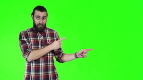 Modern man with a pigtail pointing. Modern bearded man with a pigtail pointing towards blank copy space on a bright green background, upper body side view stock video