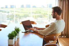 Modern man sitting at dining table with his laptop working stock photos