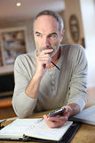 Modern man sitting at home working with smartphone and laptop Stock Image
