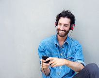 Modern man smiling with mobile phone and headphones Stock Photo