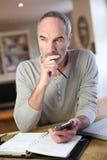 Modern man som sitter hemmastatt arbete med smartphonen och bärbara datorn Fotografering för Bildbyråer