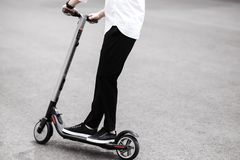 Modern man in stylish black and white outfit riding electric sco royalty free stock image