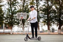 Modern man in stylish black and white outfit riding electric scooter in the city stock photos