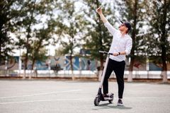 Modern man in stylish outfit making selfie while standing at the street with electric scooter stock image