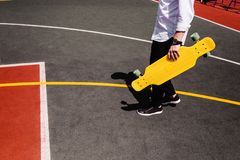 Modern man in stylish wear walks at sport playground with yellow skateboard in hand stock photo