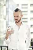 Modern man using a smartphone in the city Stock Photos