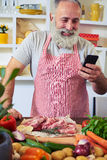 Modern man using telephone to find a recipe in the internet Royalty Free Stock Image