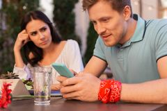 Modern man wearing red floral wrist band using his smart phone. Wrist band. Handsome blonde-haired modern men wearing red floral wrist band using his smart phone stock photos