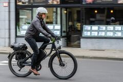 A modern man wearing white helmet rides bike in the city