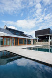 Modern mansion in front of swimming pool with blue sky. Modern mansion in front of the swimming pool with blue sky , there are glass windows and doors end of the stock images
