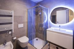 Modern marble bathroom with backlit mirror. Relaxing light. Nobody inside stock photo
