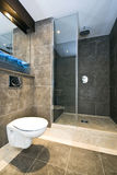 Modern marble bathroom detail. Contemporary en-suite bathroom with natural stone tiles and marble fragments in cappuccino brown Stock Photos