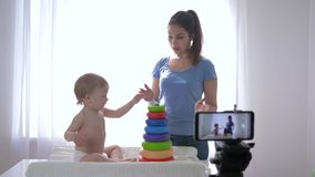 Modern marketing, merry child boy with mum vlogger played by educational toys while recording online video blog for. Followers in social networks on mobile stock video