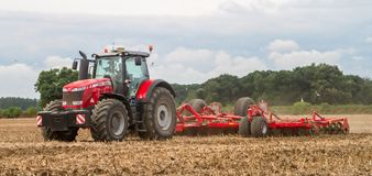 Modern massey ferguson tractor cultivating field Royalty Free Stock Images