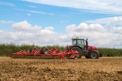 Modern massey ferguson tractor cultivating field Stock Photos