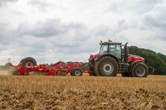 Modern massey ferguson tractor cultivating field Stock Image