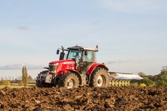 Modern massey ferguson tractor pulling a plough Royalty Free Stock Photo