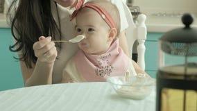 Modern matar behandla som ett barn med en sked Moderbegrepp lager videofilmer