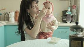 Modern matar behandla som ett barn med en sked Moderbegrepp stock video