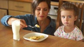 Modern matar hennes lilla dotter Flickan öppnar plikttroget hennes mun Förvanskade ägg, sund frukost, behandla som ett barn mat stock video
