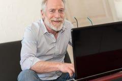 Modern mature man working on laptop Stock Photos