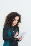 Modern mature woman, angry, use the tablet. Royalty Free Stock Photos