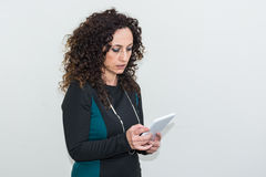 Modern mature woman, angry, use the tablet. Royalty Free Stock Image