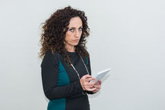 Modern mature woman, angry, use the tablet. Stock Photography