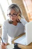 Modern mature woman using laptop at home Stock Photos