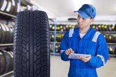Modern mechanic using tablet to check tire. Portrait of young modern technician with a blue uniform using digital tablet to check a tire Stock Photography