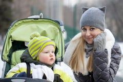 Modern med årig son två i vinter parkerar royaltyfri fotografi