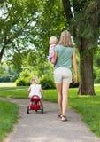 Modern med barn som in strosar, parkerar Fotografering för Bildbyråer