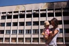 Modern med behandla som ett barn att gå nära bränd byggnad av det Mariuopl stadshuset Royaltyfri Foto