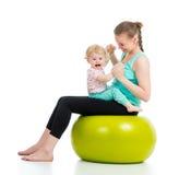 Modern med behandla som ett barn att göra som är gymnastiskt på boll Arkivfoto